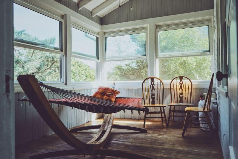 A simple summer house interior with a unique swing and a few outdoor chairs