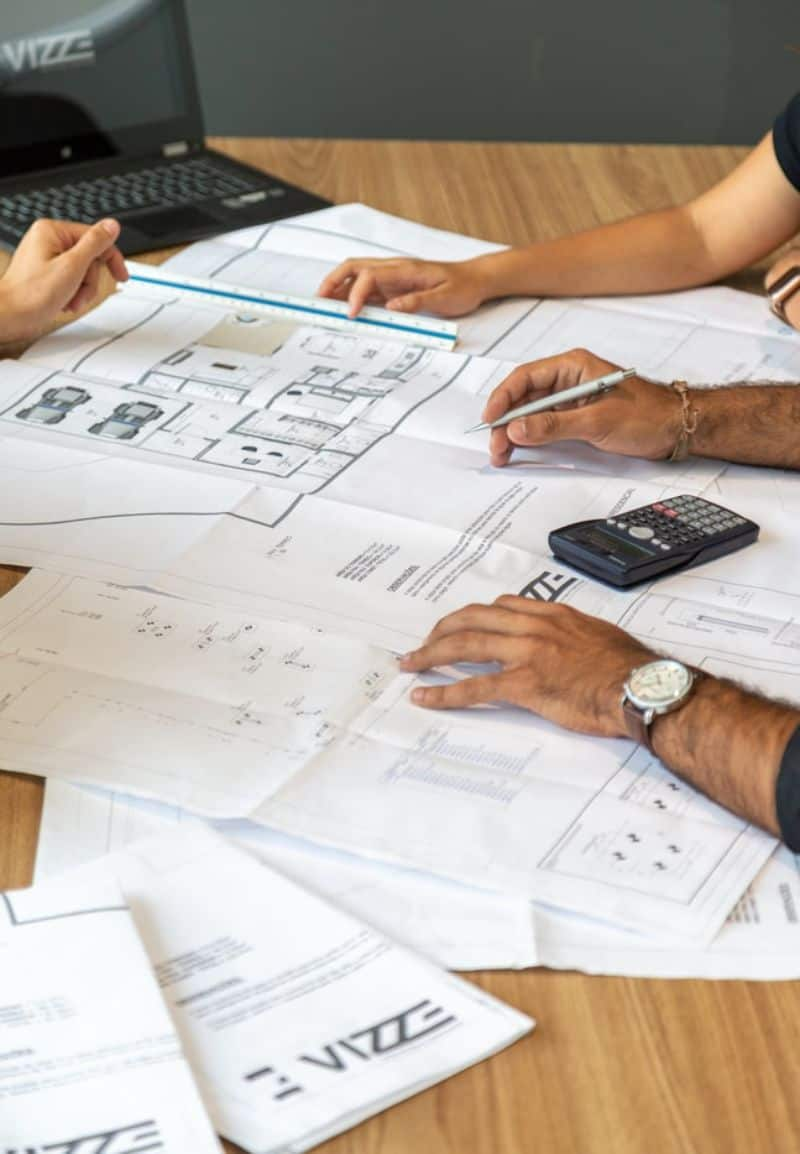 Planning sheets on a table with various hands