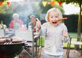 Happy child holding a sausage and thumbs up at a BBQ
