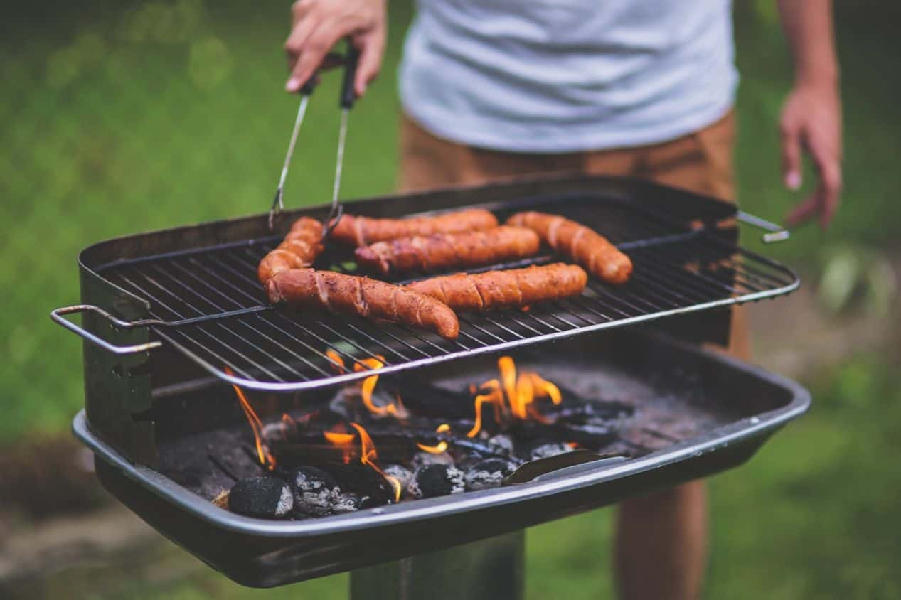 bottom half of someone at a small raised charcoal grill with sausages on top