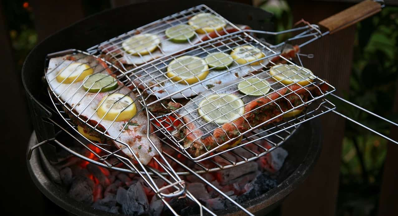 fish in a grilling basket with citrus slices