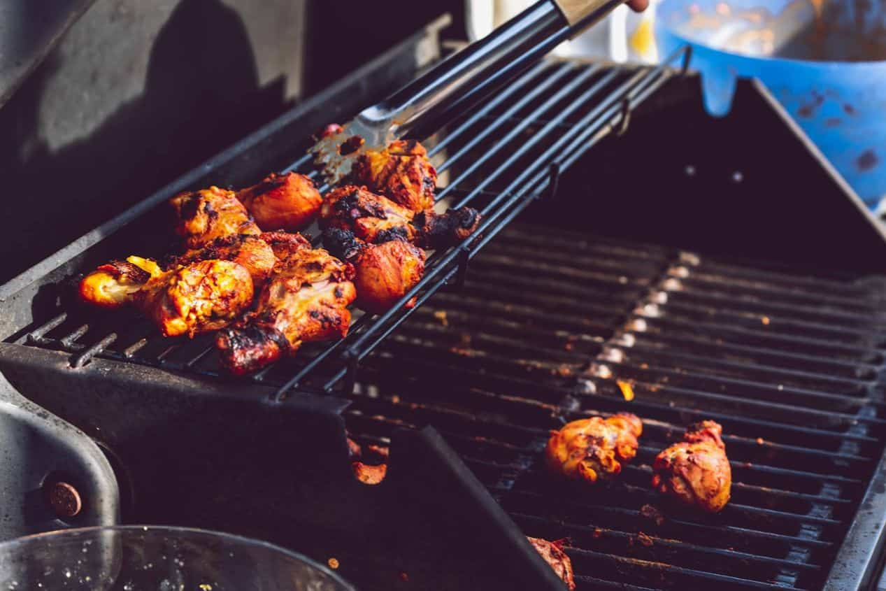 chicken on a bbq with utensils