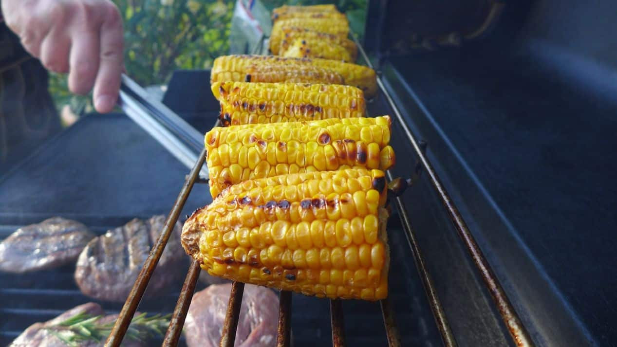 corn on the top shelf of a bbq grill with burgers below it and a hand with tongs