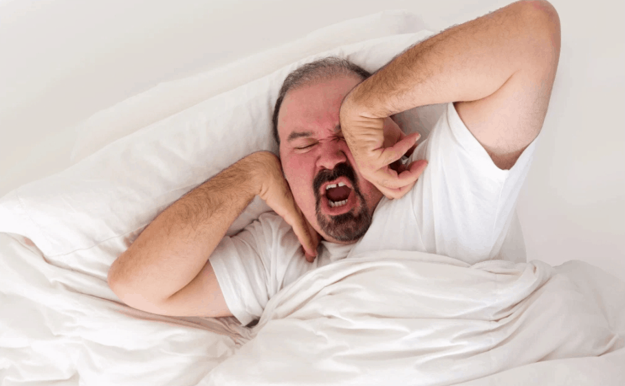 Man in bed yawning