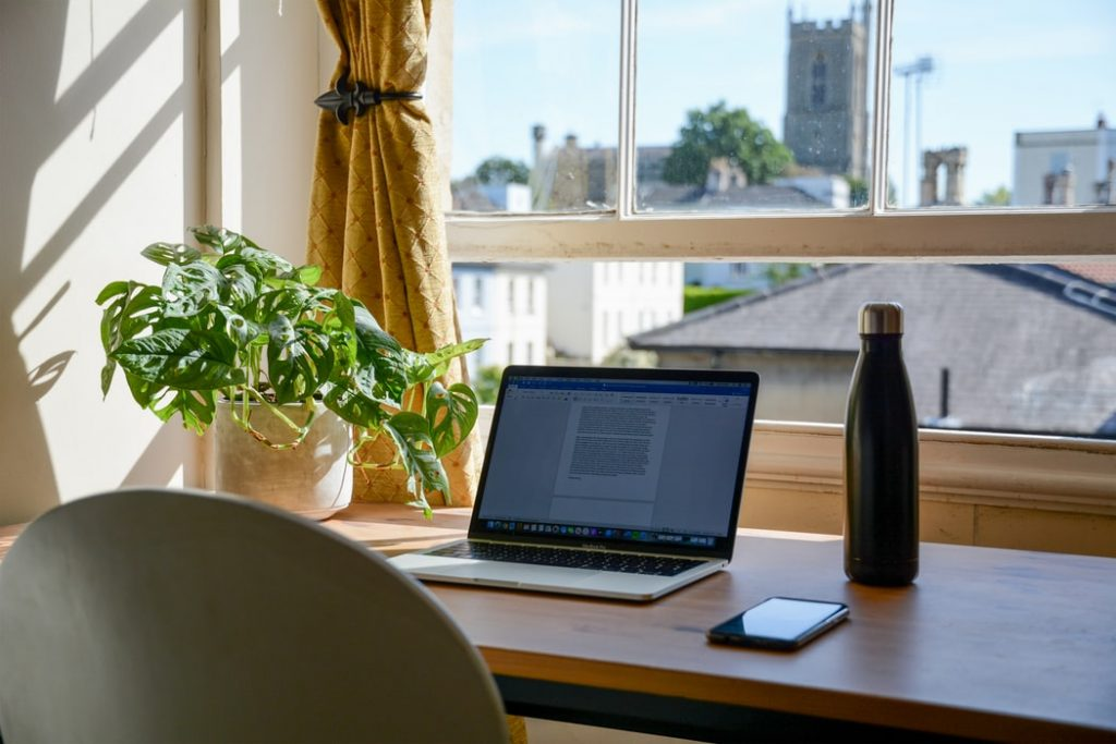 a laptop on a desk next to plant and water bottle looking through a window to a church spire
