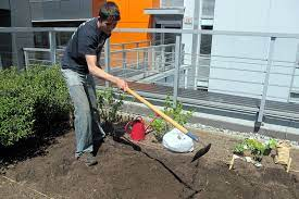 man hoeing a small roof garden