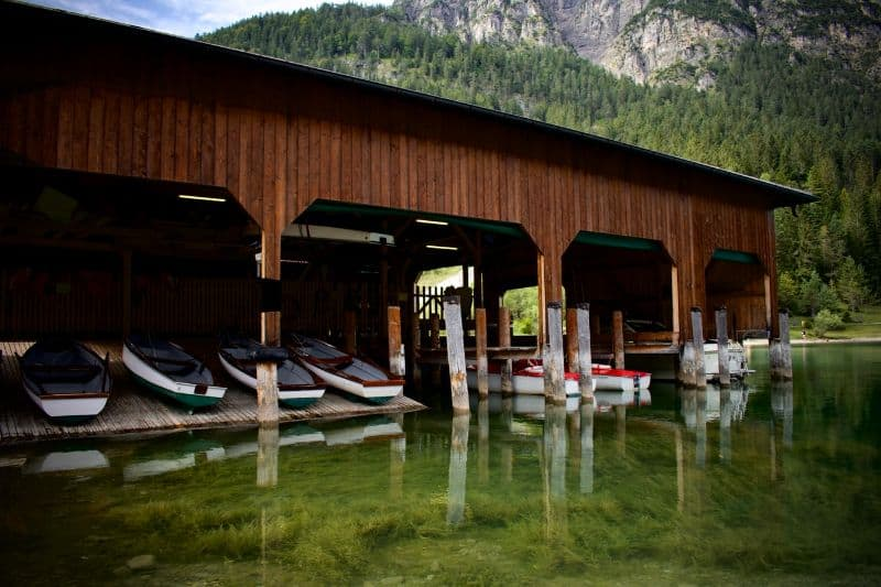 log cabin boat store with boats moored in green waters at the foot of a mountain