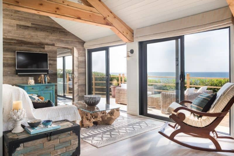 log cabin interior with rocking chair and wall-mounted TV looking out over veranda and past foliage to the sea