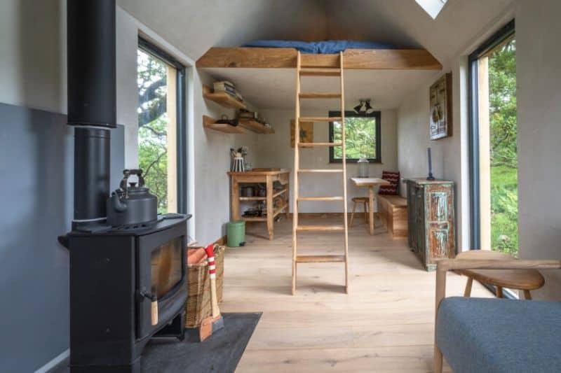 Kindred Log cabin interior with wood burner and ladder to loft bunk bed