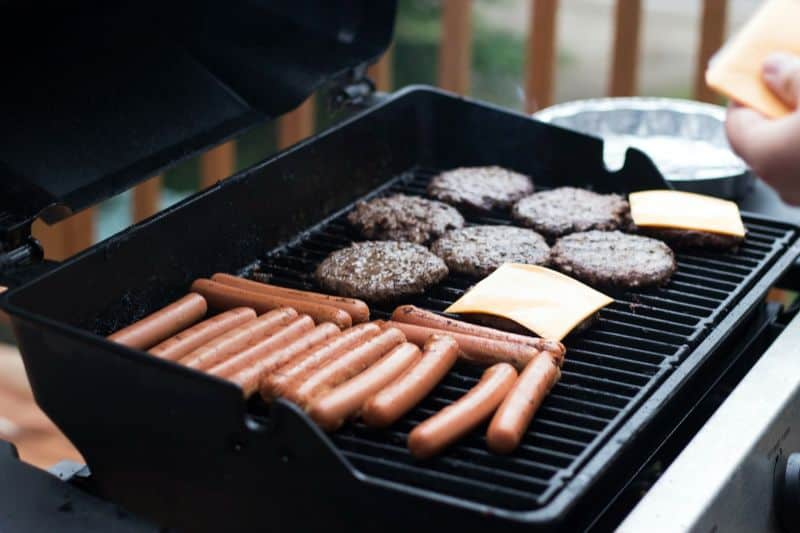 burgers, sliced cheese, and sausages cooking on BBQ