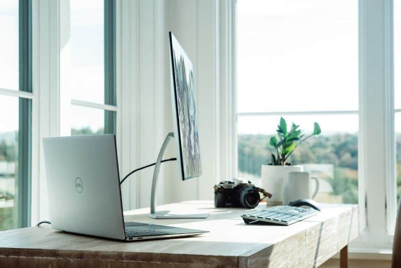 Work from home space with open Dell laptop and monitor with a keyboard on a desk with a mug, camera, and potted plant backed by floor-to-ceiling windows