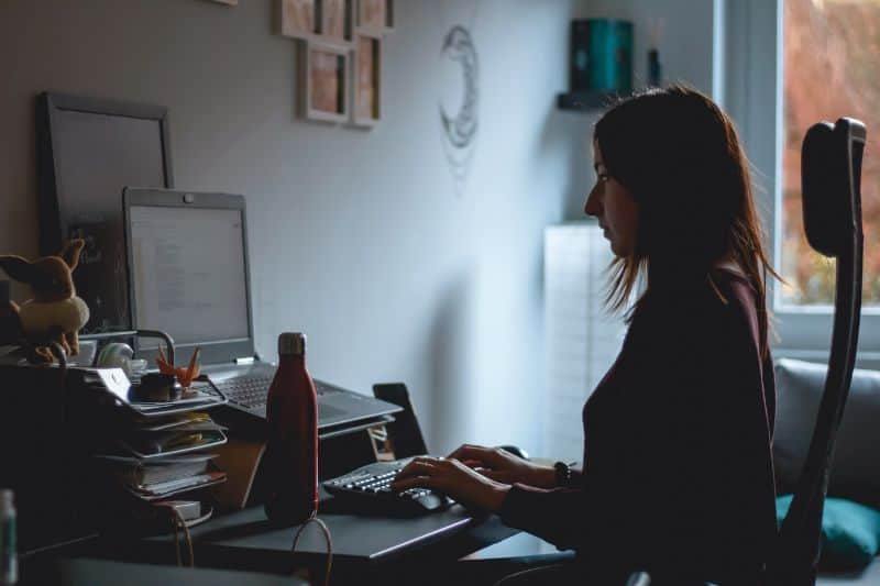 woman working in a shadowy/dark office at a desk on a laptop with a water bottle