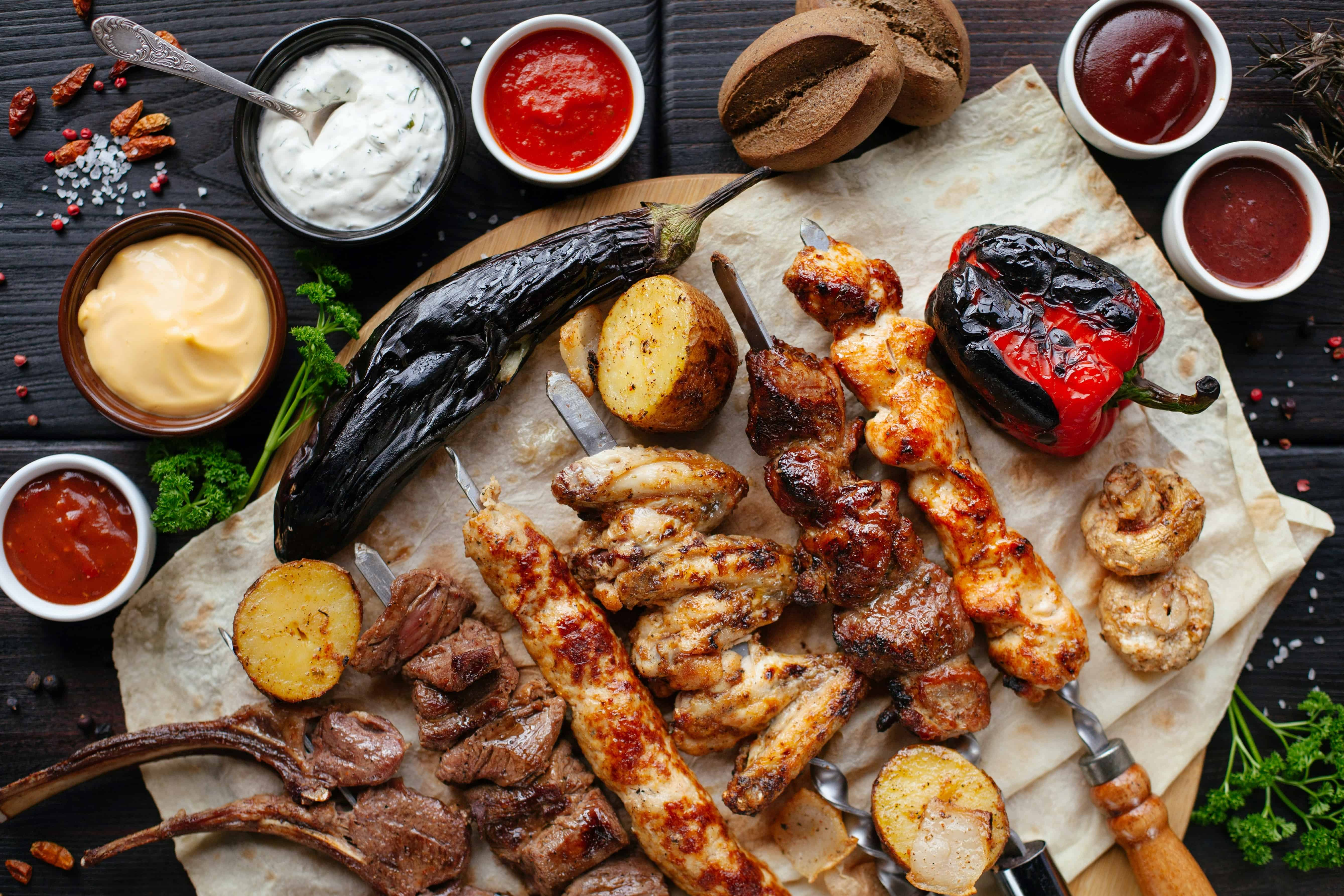 bbq skewers, vegetables and condiments on a table