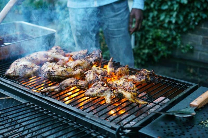 chicken cooking on open fire charcoal grill