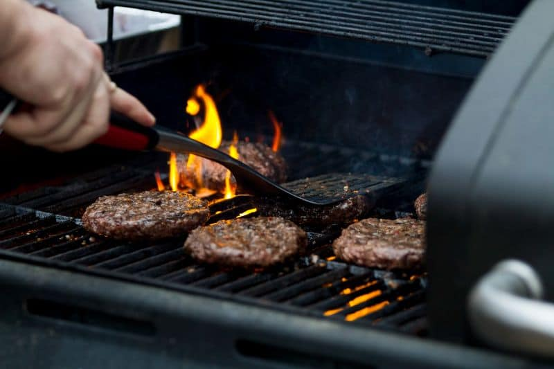 hand patting down burgers on a charcoal grill with spatula