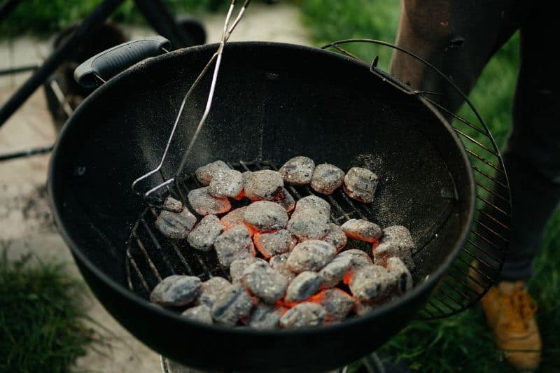 kettle charcoal bbq filled with white hot coals and someone tending them with tongs