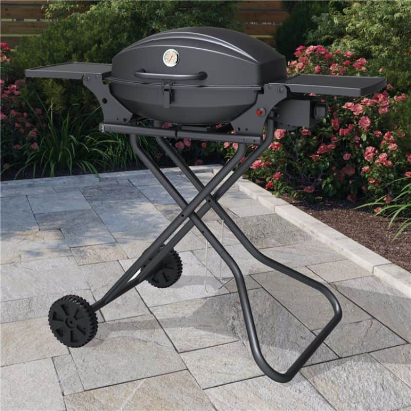 BillyOh Tennessee portable black tabletop BBQ on wheels on a patio with flowers