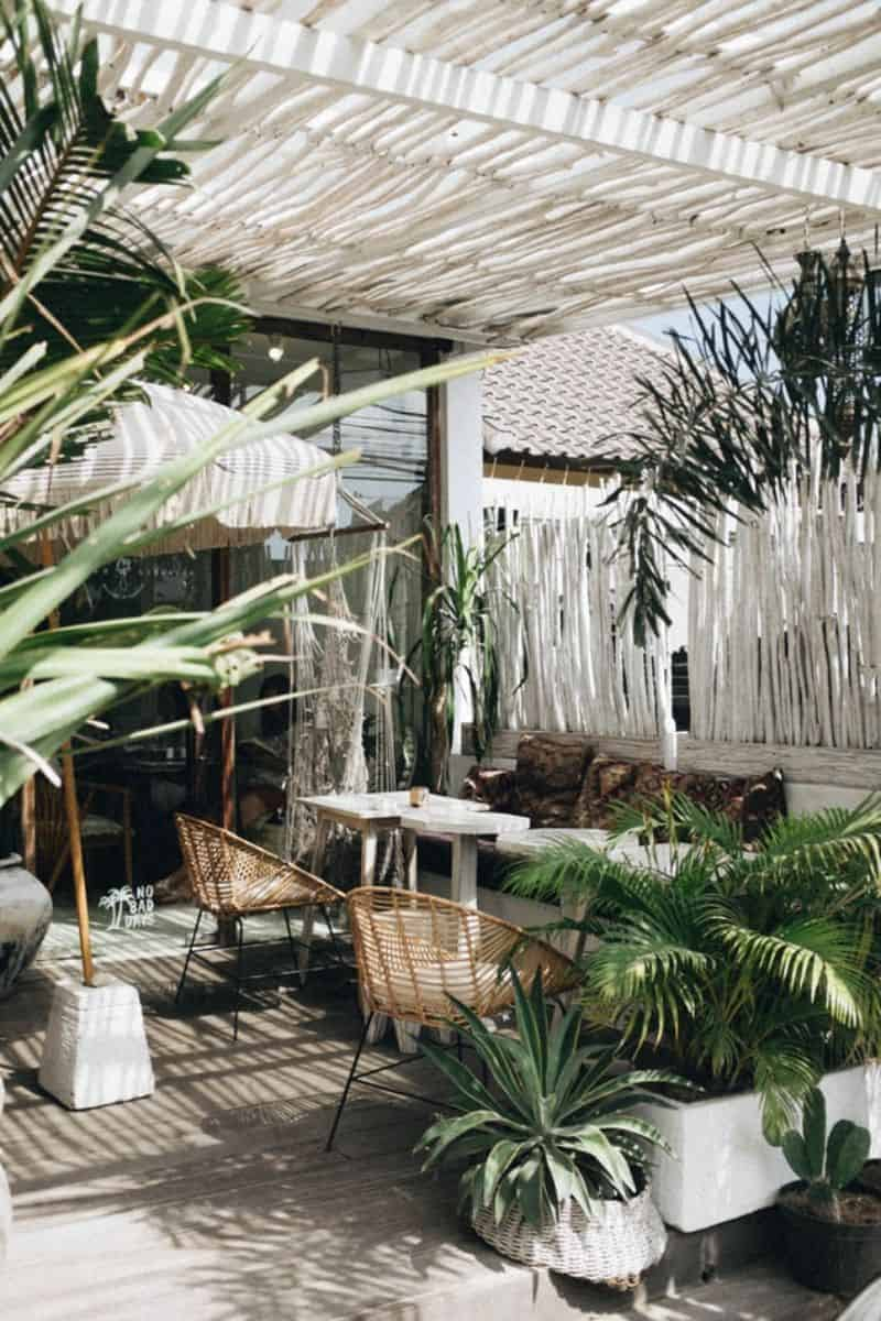 all white themed patio with umbrella and plants