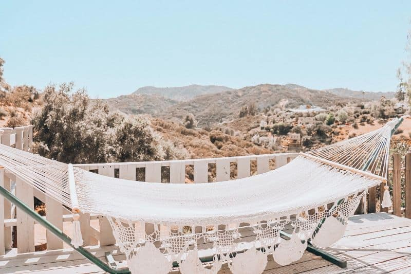 white hammock on a porch overlooking foothills in the sun