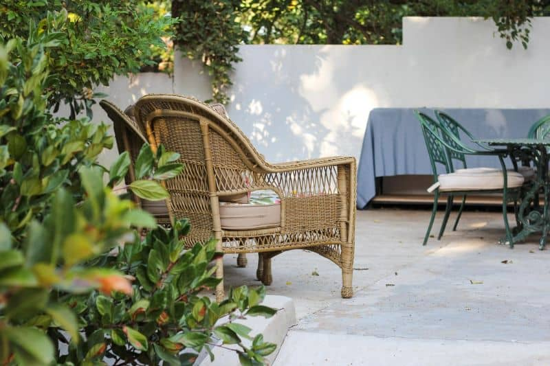 rattan garden chair on a patio with white walls and creepers