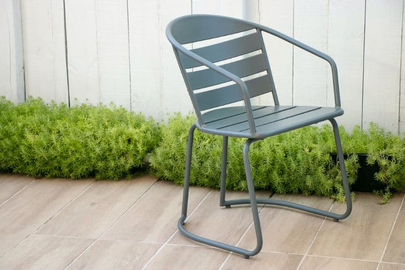 aluminium chair on patio tiles next to low green bushes
