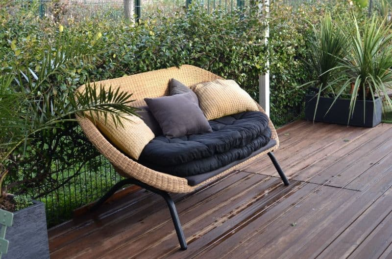 natural rattan loveseat with cushions on deck surrounded by plants
