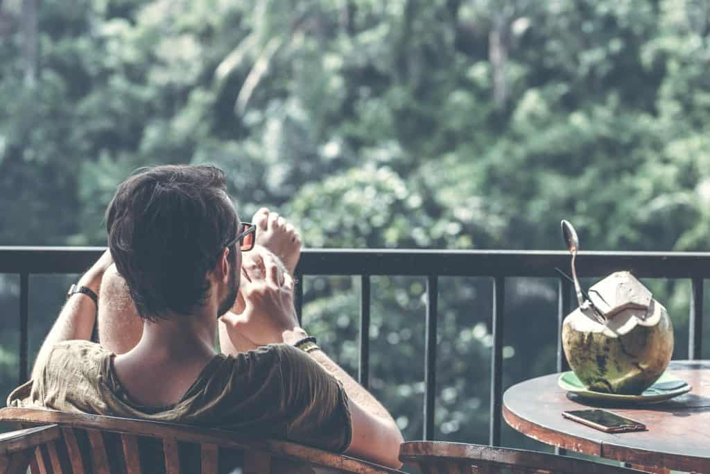 over the shoulder of Man with feet up on balcony with a coconut on the table