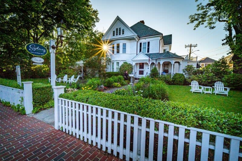 white picket fence house set back on a lawn