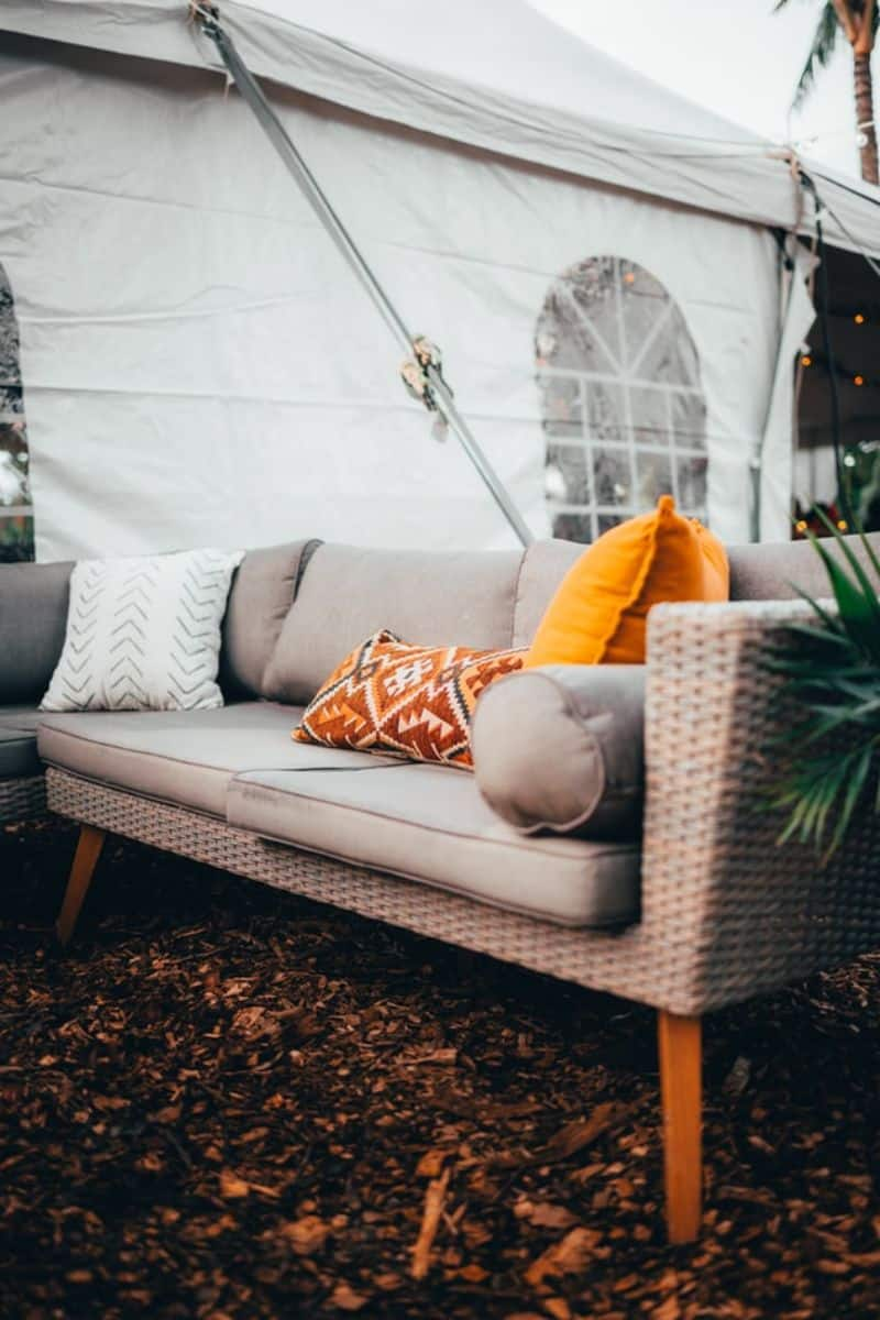 rattan outdoor sofa next to a marquee