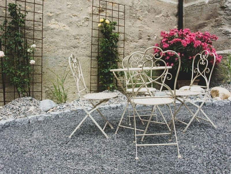 small metal patio set on a gravel courtyard
