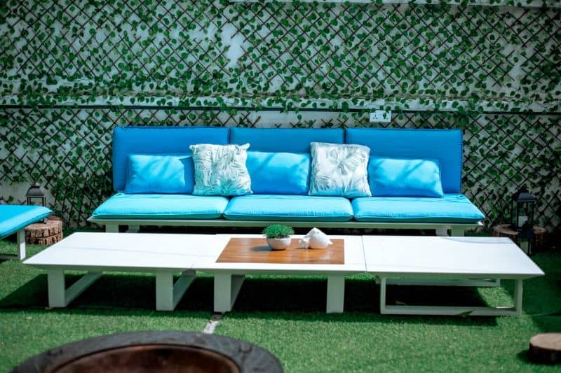 patio furniture with blue cushions and a long low table on astro turf