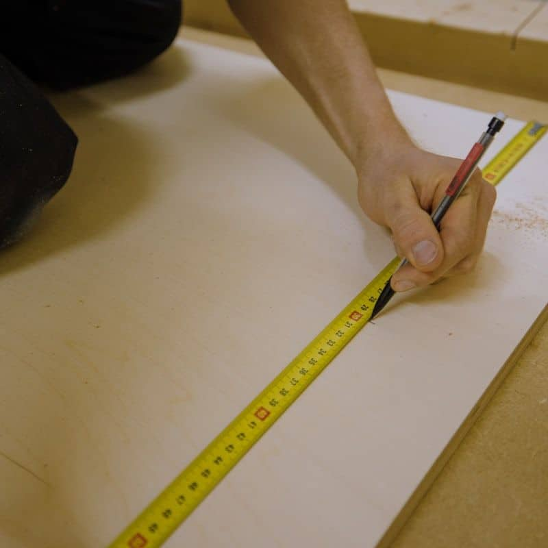 measuring tape with hand marking a piece of wood in pencil