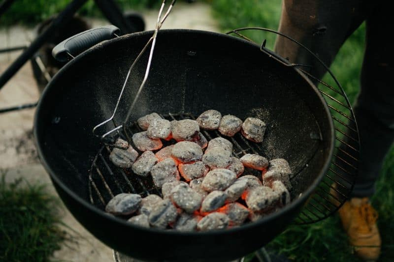 Burning charcoal briquettes on a kettle grill