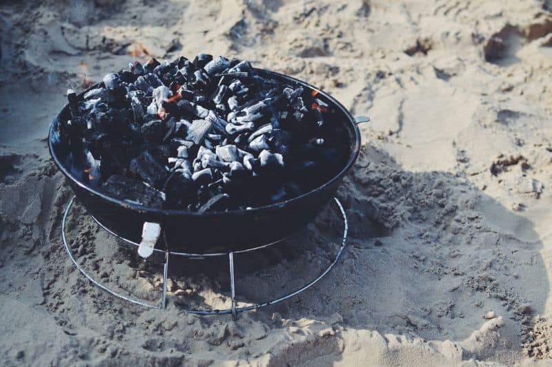 Burning lump hardwood charcoal on a portable charcoal grill on sand