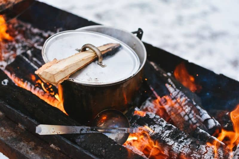 A pot on the grill with a wood stake through the handle