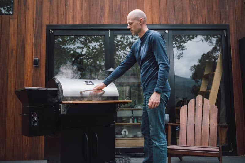 A man setting up his smoker grill outdoors