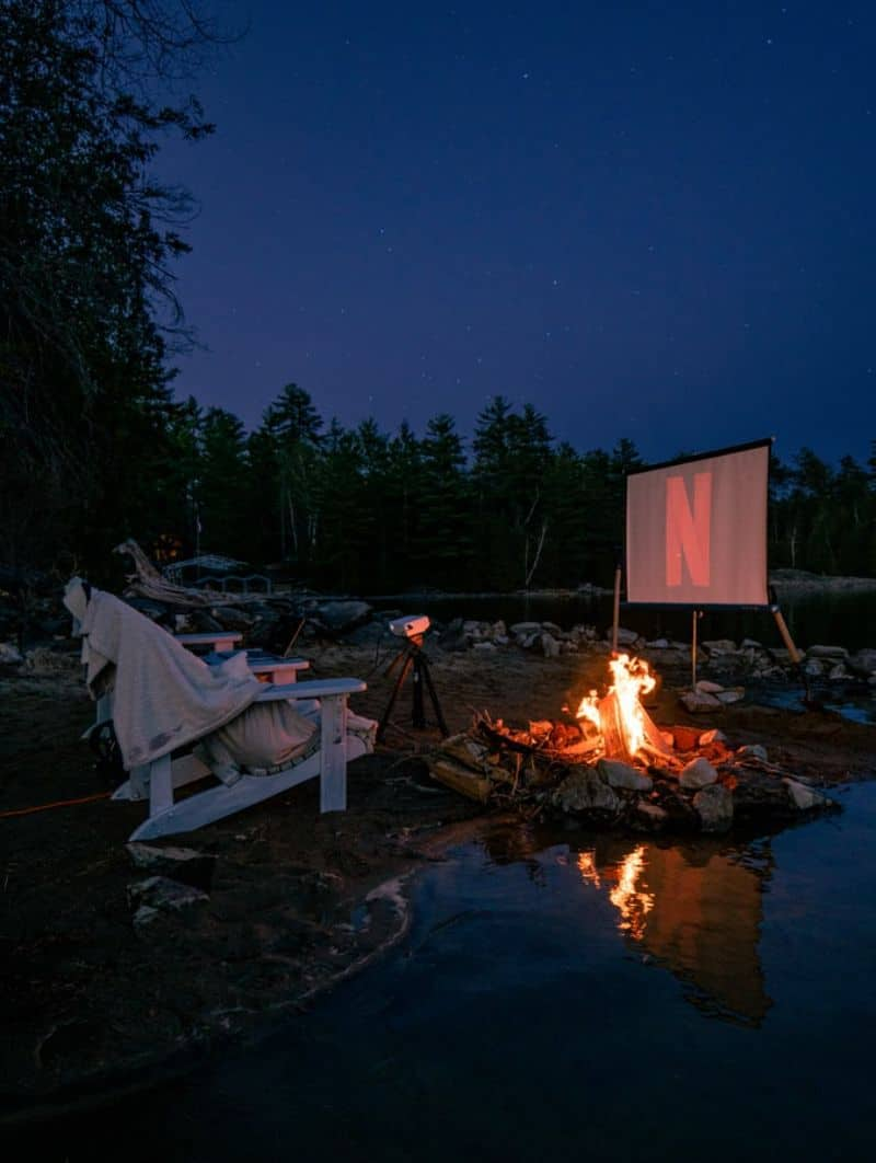 A cosy set-up for an outdoor home cinema with a bonfire and large Netflix logo on projector