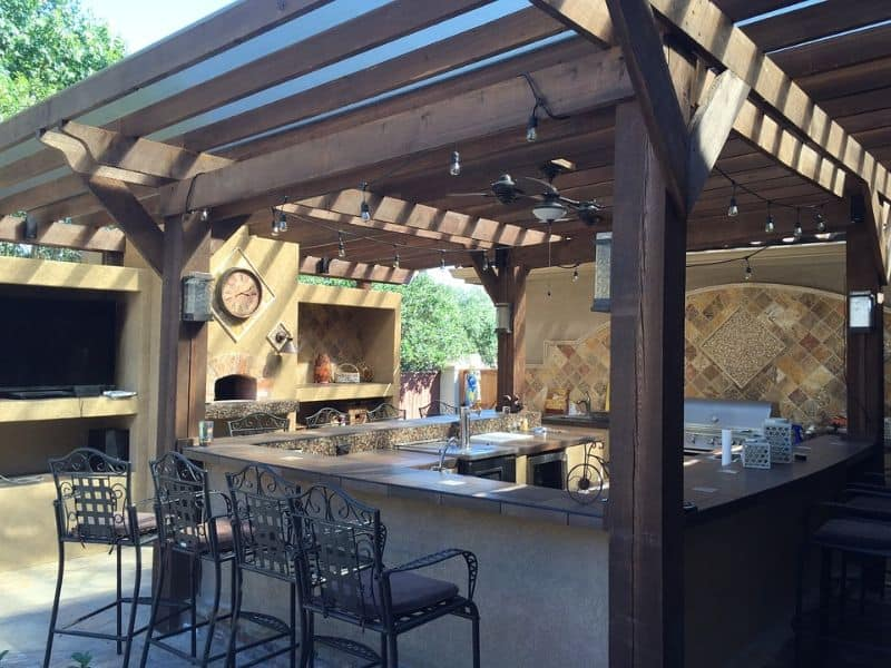 A pergola style outdoor kitchen space with built-in grill, countertop and bar stools
