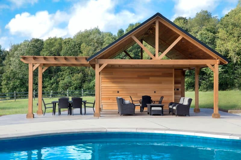 A backyard pool with rattan garden furniture in a pool shed