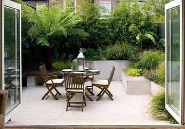 Tall walls covered in plants and a simple table outdoors