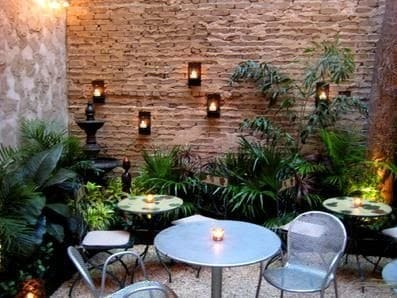 Bricks and plants with some hanging lights, creating a cosy dining space