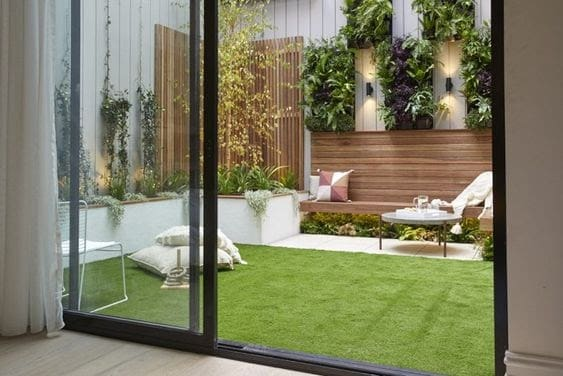 A small backyard with low-maintenance artificial grass and comfy garden cushions