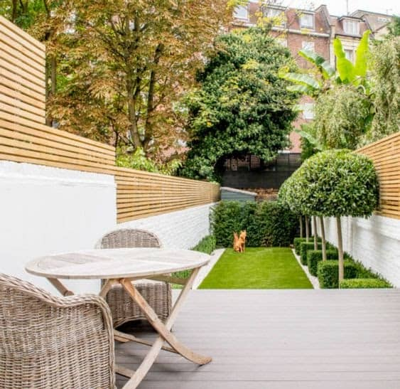 A long, narrow garden with a comfortable seating area on the deck, modern fencing and a section of grass