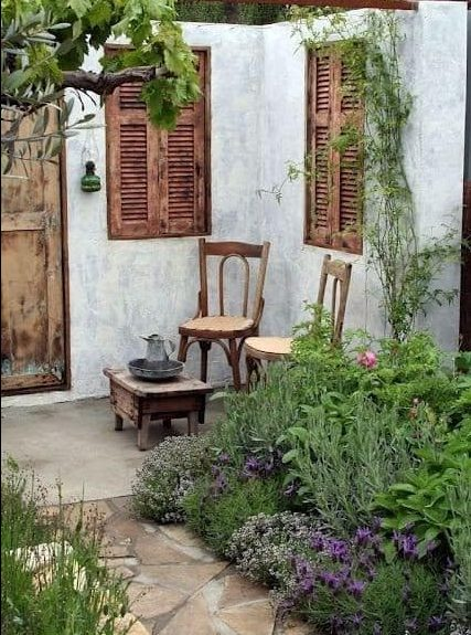 A french country garden with two small chairs and a couple of rustic shutters