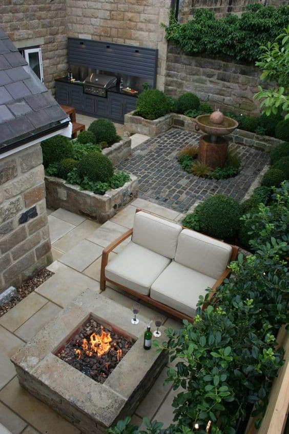 A small garden with firepits, fountains and foliage