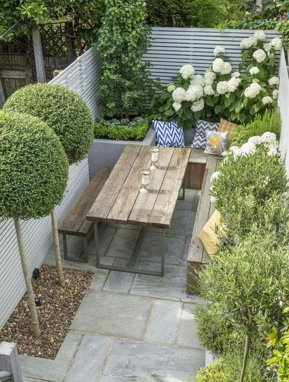 A small backyard living space with picnic table for al fresco dining