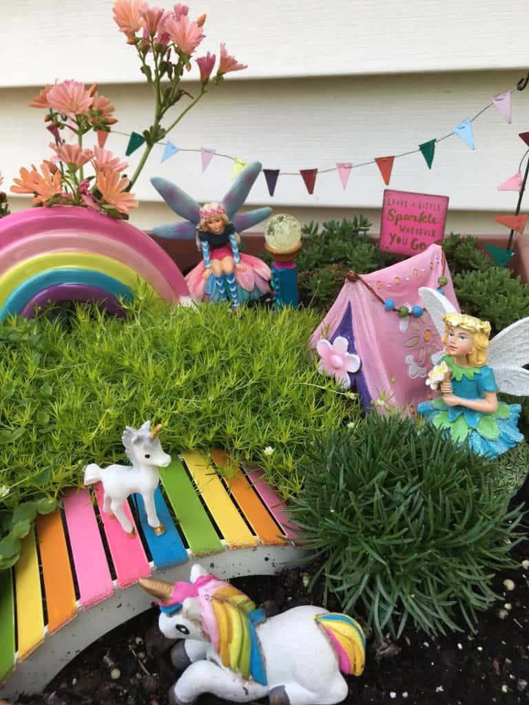 Fairy and unicorn garden with rainbow and colourful bridge