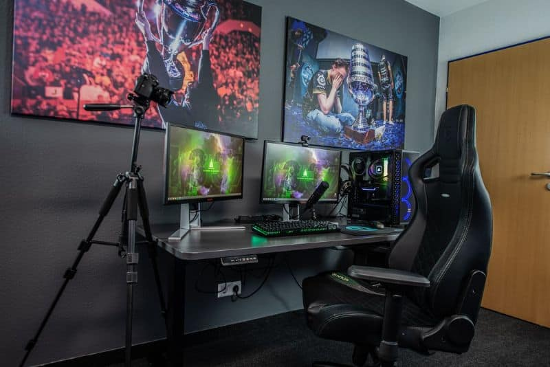 A gaming room set-up with two computer monitors, electric adjustable gaming table, and a contemporary gaming black gaming chair.