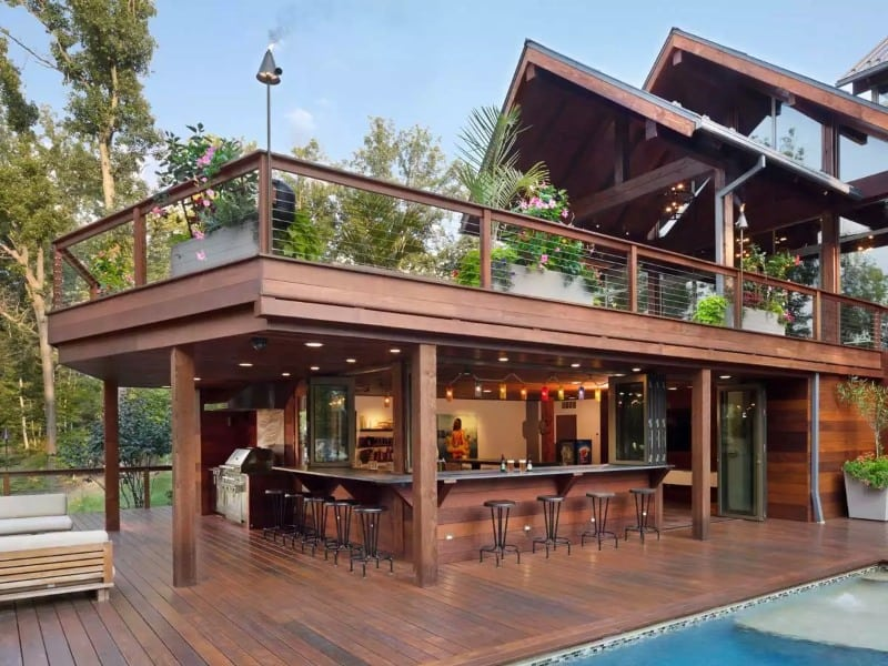 A huge yard that features an L-shaped bar on wood decking and a pool