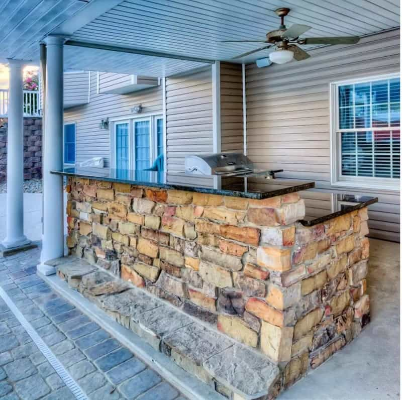 Patio bar with exposed stones, fan, and BBQ in the background